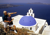 A senior tourist couple look out over the traditional dome roof of a Greek orthodox church and across the Mediterranean Sea. Santorini, Greece.