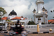 A motorcyclist rides past the main mosque in the UNESCO heritage city of Georgetown in Penang, Malaysia. Photo: Sanjit Das/Panos