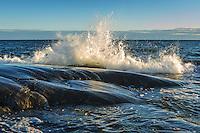 Brytande havsvåg mot svart klipphäll på Torö i Stockholms skärgård