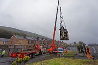 Pictured: The Banksy is hoisted by a crane onto a flat bed lorry. Wednessday 29 May 2019<br /> Re: Contractors are working to move Banksy's Season Greeting, now owned by John Brandler, which appeared on a garage wall in Port Talbot, to a new location in the same town in south Wales, UK.