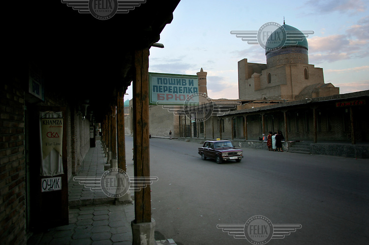 A taxi drives through the old city with the Po-i-Kalyan mosque in the background.