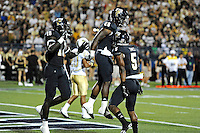 17 September 2011:  FIU running back Darriet Perry (28) celebrates his second-half touchdown with wide receiver Wayne Times (5) and wide receiver Glenn Coleman (10) as the FIU Golden Panthers defeated the University of Central Florida Golden Knights, 17-10, at FIU Stadium in Miami, Florida.