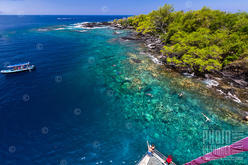Tourists on a catamaran cruise marvel at the clear waters of Hawai'i Island's Kealakekua Bay. Swimmers and snorkelers enjoy the water near the shore.
