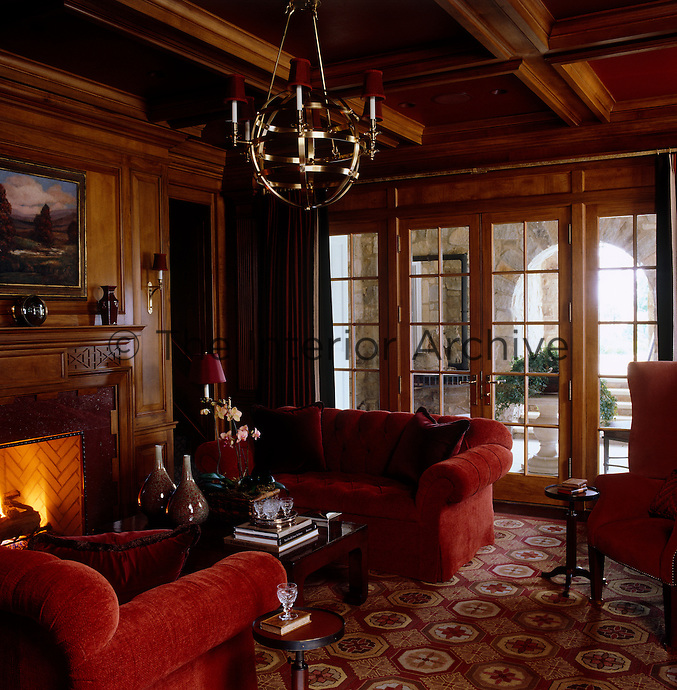 A womb-like snug; the warm and cosy atmosphere comes from a roaring fire, the comfortable red velvet sofas and the mellow tones of the wood panelling on the walls and ceiling