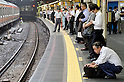 Tokyo, Japan - A Japanese salaryman squats down for a break at Shinjuku Station. Morning commuters typically spend over one hour on the train going to work. Trains are usually so packed that train platform staff have to push commuters to fit in the train so that the doors can close shut. (Photo by Yumeto Yamazaki/AFLO)