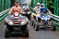 Rough looking gang of young ATV riders following their leader.