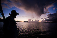 Man looking at squall at sunset aboard yacht
