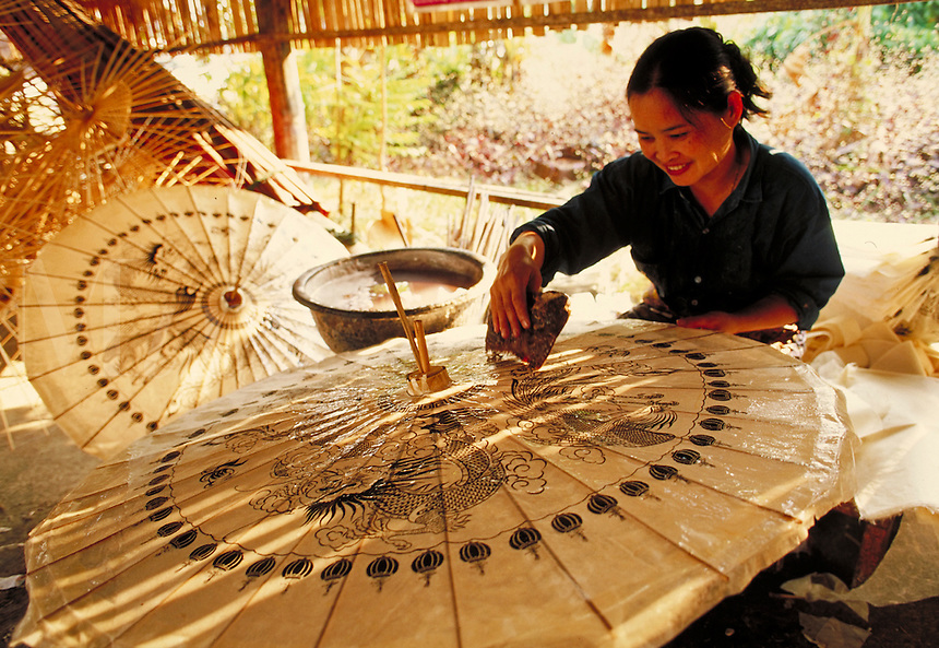 A woman applies decals to a paper umbrella. Chiang Mai, Thailand. Chiang Mai, Thailand.
