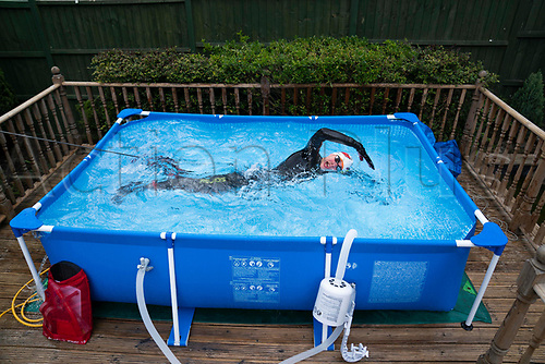 2April 30th 2020, NEWCASTLE-UNDER-LYME, United Kingdom; British triathlete Lloyd Bebbington trains in a temporary swimming pool in his garden because of the coronavirus lockdown restrictions in Newcastle-under-Lyme