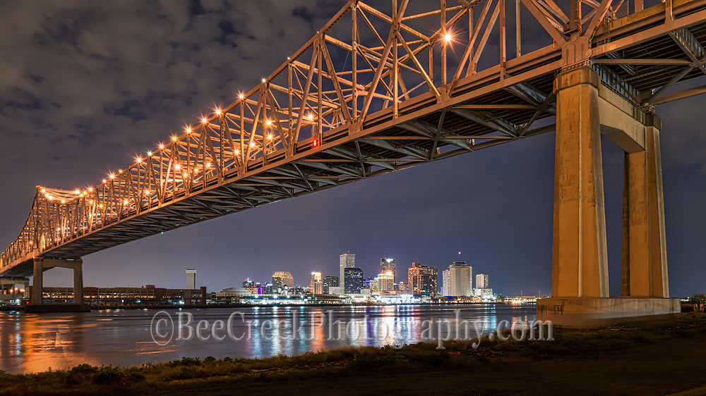 A view of New Orleans skyline from under the Mississippi bridge as the city was lite up along with the skyline reflecting back into the water from accross the river.
