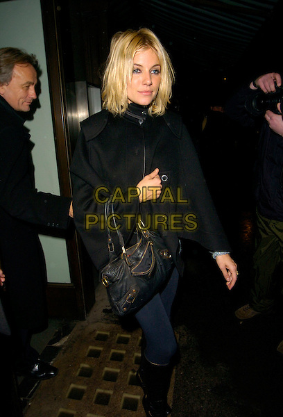 SIENNA MILLER.Celebration Of Film Dinner, Cecconi's, Burlington Gardens, London, England, February 9th 2007..full length black coat Balenciaga bag navy blue tights knee high boots funny eyes drunk?.CAP/CAN.©Can Nguyen/Capital Pictures