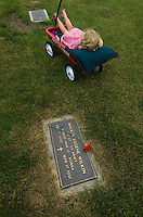 A girl relaxes in a red wagon next to a veterans bronze grave marker with red carnation placed on it on Memorial Day.