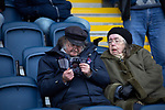 Two elderly home supporters reading the match programme in the main stand before AFC Fylde took on Aldershot Town in a National League game at Mill Farm, Wesham. The fixture was played against the backdrop of the total postponement of all Premier League and EFL football matches due to the the coronavirus outbreak. The home team won the match 1-0 with first-half goal by Danny Philliskirk watched by a crowd of 1668.