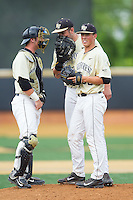 Matt Conway (center) has a meeting on the mound with catcher Ben Breazeale (9) and relief pitcher Parker Dunshee (36) during the game against the Virginia Cavaliers at Wake Forest Baseball Park on May 17, 2014 in Winston-Salem, North Carolina.  The Demon Deacons defeated the Cavaliers 4-3.  (Brian Westerholt/Four Seam Images)