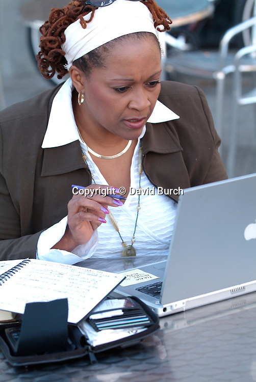 African American working on laptop, concentrating