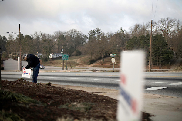 January 24, 2008. Spartanburg, SC.. Presidential candidate and former US senator, John Edwards campaigned across the western part of South Carolina today in an effort to shore up support before Saturday's primary election.. A supporter puts up signs before the candidate arrived.