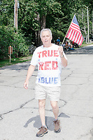 """A man holds an American flag while wearing a shirt reading """"True red, white, and blue"""" as he marches in the 4th of July Parade in Amherst, New Hampshire, on Thu., July 4, 2019."""