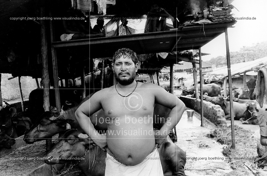 INDIA Maharashtra Mumbai Bombay, worker in buffalo shed in living quarter Andheri East, fresh buffalo milk is sold directly to customer  / INDIEN Mumbai, Stall mit wasserbueffeln in einem Wohnviertel, die Milch wird frisch an die Kinden verkauft - copyright Joerg Boethling, Also as signed black&white fine print available.