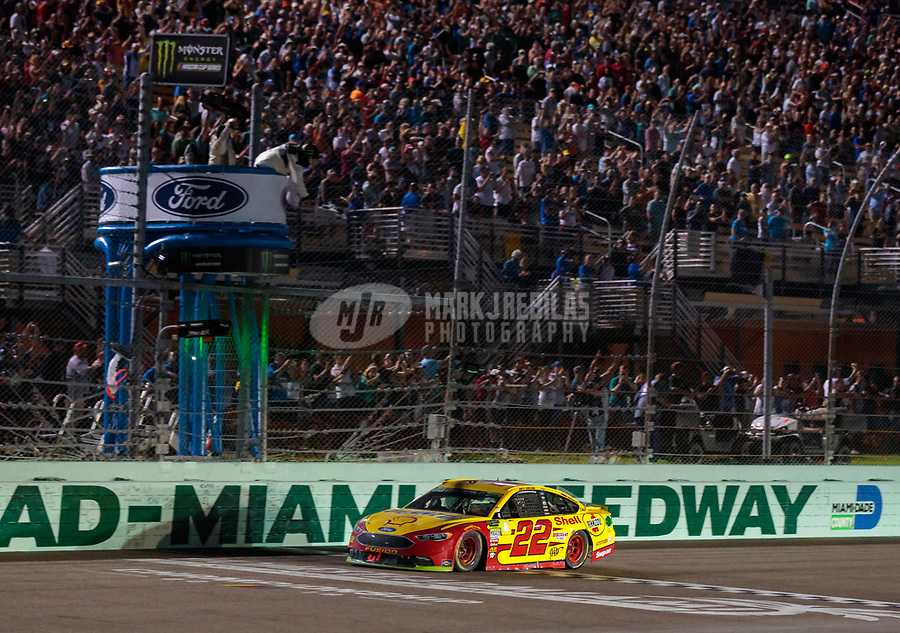 Nov 18, 2018; Homestead, FL, USA; NASCAR Cup Series driver Joey Logano (22) takes the checkered flag to win the Ford EcoBoost 400 and the NASCAR Cup Series championship at Homestead-Miami Speedway. Mandatory Credit: Mark J. Rebilas-USA TODAY Sports