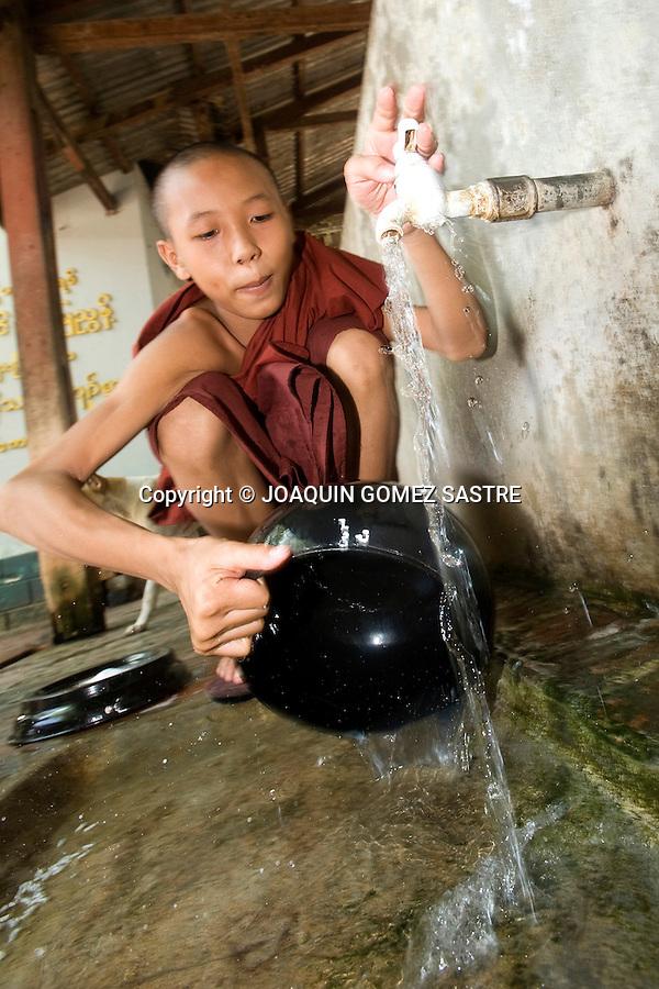 Un joven novicio  se dispone a llenar un cuenco de agua en un monasterio en Bagan (Myanmar).foto © JOAQUIN GOMEZ SASTRE