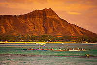 Outrigger canoe teams race past Diamond Head to Waikiki Beach.
