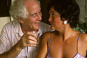 Rio de Janeiro, Brazil. Train robber Ronnie Biggs with girlfriend Eva relaxing with a brandy at home in Santa Tereza, 1988.