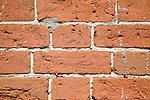 Red brick wall with white mortar joints and holes created by insects