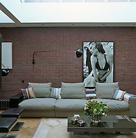Behind the grey flannel sofa in the living room the exposed brick wall displays a large framed black and white photographic print
