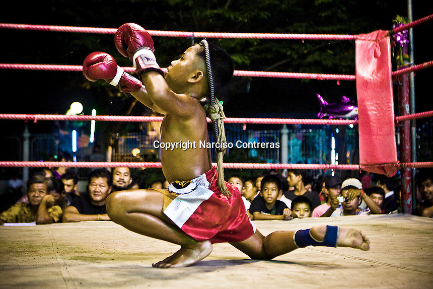 A young kid fighter is performing the ritual dance called  Wai khru ram muay before fighting in a Nonthaburi fair district. He is fighting for a prize of 300 bath (10 american dollar). The Muay Thai fighting is a national sport in Thailand, ritual and  brave strength, but it´s  has became a way to livelihood for many disinherited families and a dream to has a muay thai champion among them as well.