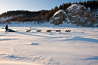 Tom Lesatz runs past rock cliffs on the Yukon River shorlty after leaving the village checkpoint of Ruby in Interior Alaska during the 2010 Iditarod