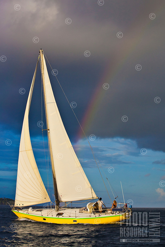 Couple sailing in Tahiti with rainbow in the background