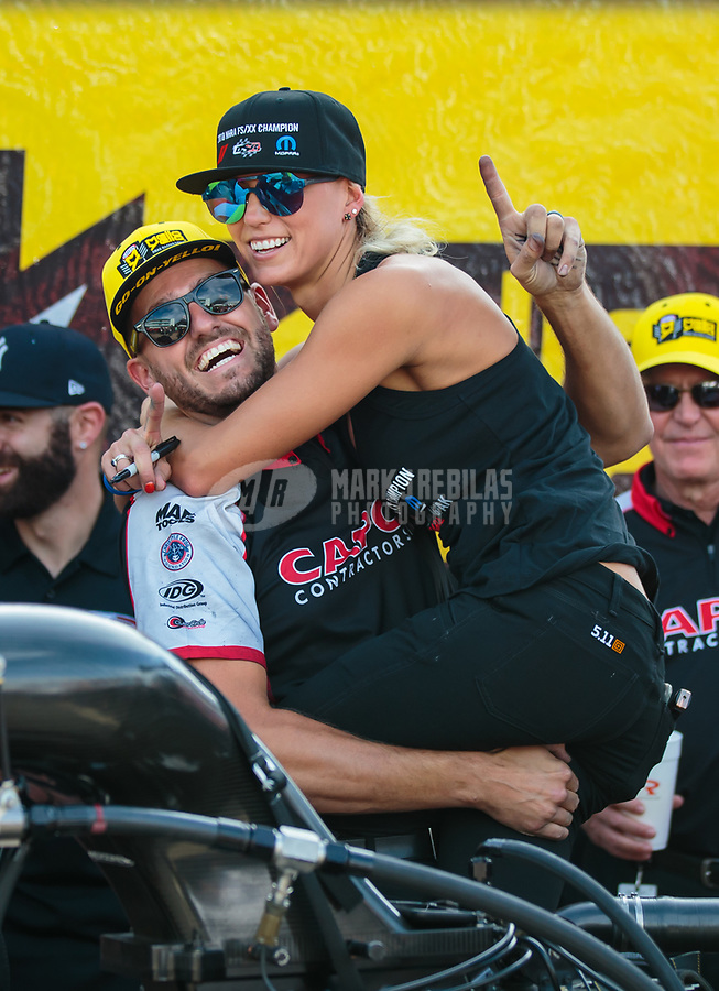 Oct 7, 2018; Ennis, TX, USA; Gary Pritchett, crew member for NHRA top fuel driver Steve Torrence (not pictured) celebrates with wife Leah Pritchett after winning the Fall Nationals at the Texas Motorplex. Mandatory Credit: Mark J. Rebilas-USA TODAY Sports