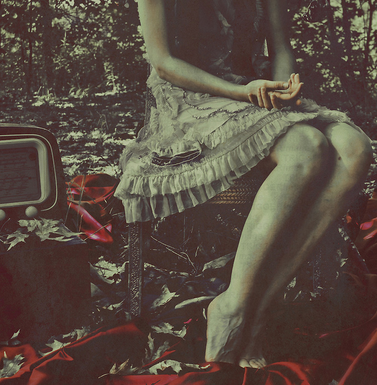 Female youth sitting alone on an old chair outdoors in woods beside an old fashioned radio
