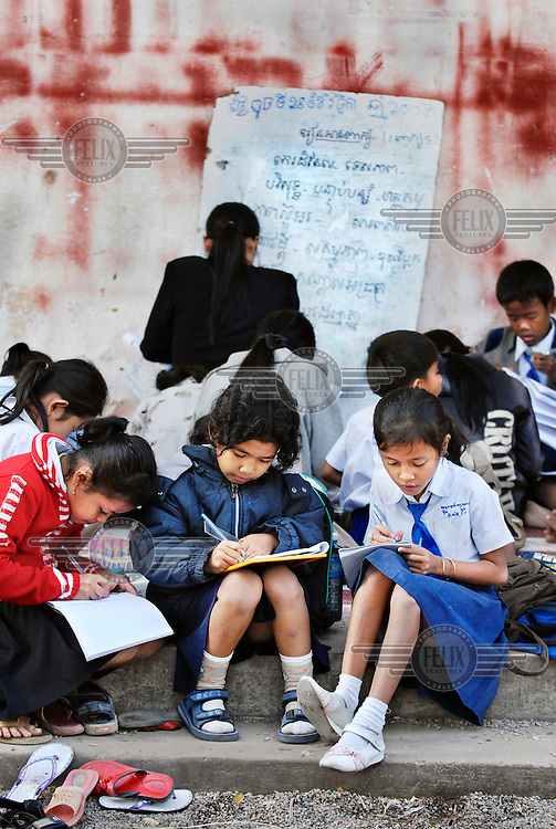School children having a lesson outside in a crowded and dilapidated old school.