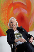 The supremely glamorous and vivacious Anne Madden photographed in front of one of her vibrant paintings entitled Odyssey & Icarus