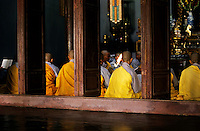 Group of Buddhist monks praying together inside their pagoda, Vietnam.