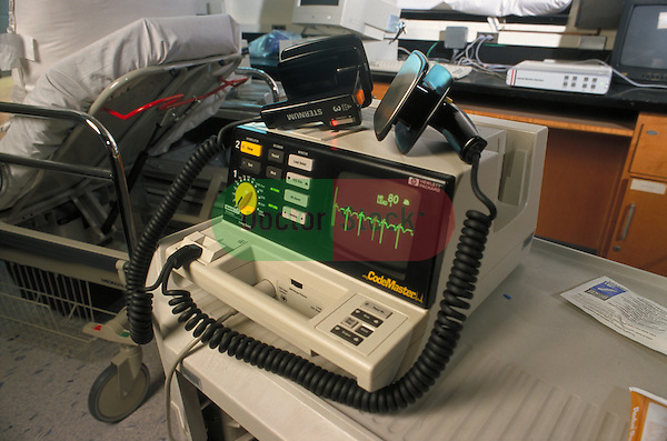 still-life of defibrillator on table next to gurney in hospital emergency room