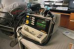 still-life of defibrillator on table next to gurney in hospital emergency room