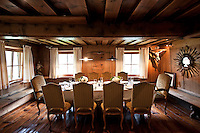 The dining room has a low beamed ceiling and long wooden benches lining the walls, and a table laid for dinner