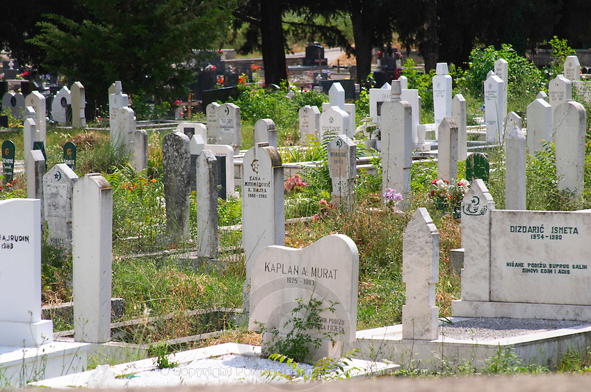 A grave yard church yard burial place with many recent graves with narrow and high white grave stones. Trebinje. Republika Srpska. Bosnia Herzegovina, Europe.