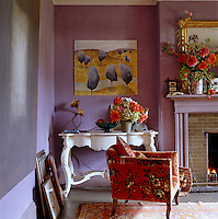 A white-painted French console table stands in the corner of the living room behind an armchair covered in turn-of-the-century American chintz