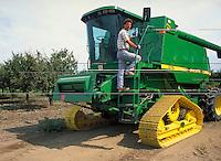 young farmer climbing on to green harvester equipment. farmer. California.
