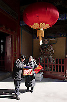 Two worshippers look at the auspicious signs collected from Dongyue Temple for the Chinese New Year in Beijing, China, on February 15, 2010.