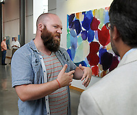 STAFF PHOTO BEN GOFF  @NWABenGoff -- 07/18/14  Jerad Sears, worship arts pastor at Grace Point Church, greets visitors during the grand opening of STORY: The Galley at Grace Point at Grace Point Church in Bentonville on Friday July 18, 2014. The gallery opened with an exhibit of paintings titled 'Connecting the Dots' by artist Heidi Carlsen-Rogers of Bella Vista.