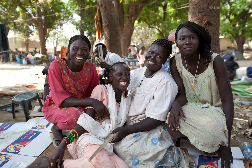 15 december 2010 - Juba, South Sudan - Paulina Awat, 61 years old, sits with her three daughters on the bank of the river Nile in the southern capital Juba, South Sudan. Paulina, her husband and their 5 children spent 13 days on the boat that brought them from Khartoum to Juba. The family spent 25 years living in the North. Over 55.000 southerners have returned to the South to vote in an independence referendum on January 9, 2011. The return has been organized by the autonomous Government of Southern Sudan programs and others haves spontaneously returned to various states across the south. Many Southern Sudanese fled to the north during the second north-south civil war, which began in 1983 and ended with a 2005 peace deal that granted the south the right to secede through a referendum. Photo credit: Benedicte Desrus