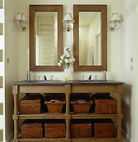 An oak vanity table with a Belgian stone top in the bathroom has wicker baskets for storage