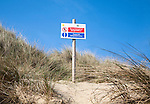 Sign informing that sand dunes are part of the sea defence and to use designated routes, Horsey, Norfolk, England