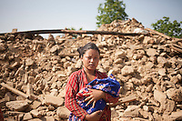 A woman stands in front of her destroyed house at Jalkeli village, outskirts of Kathmandu, Nepal. May 1, 2015