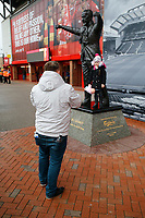 17th November 2019; Anfield, Liverpool, Merseyside, England; Womens Super League Football, Liverpool Women versus Everton; A father photographs his child alongside the statue of legendary Liverpool manager Bill Shankly outside the Kop end of the ground  - Editorial Use
