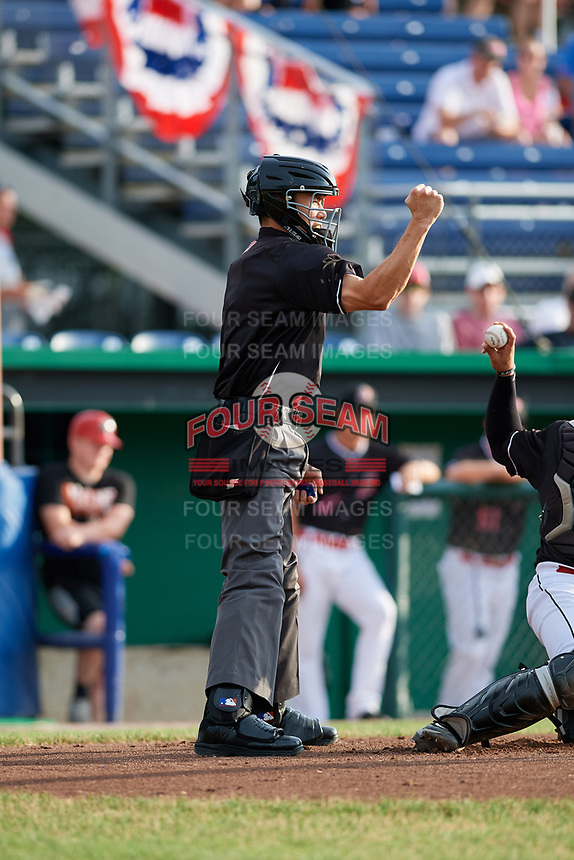 Home plate umpire Jae-Young Kim calls a strike during a game between the West Virginia Black Bears and the Batavia Muckdogs on July 2, 2018 at Dwyer Stadium in Batavia, New York.  West Virginia defeated Batavia 3-1.  (Mike Janes/Four Seam Images)